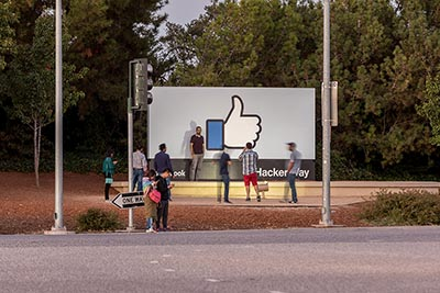 People standing in front of Facebook headquarters sign