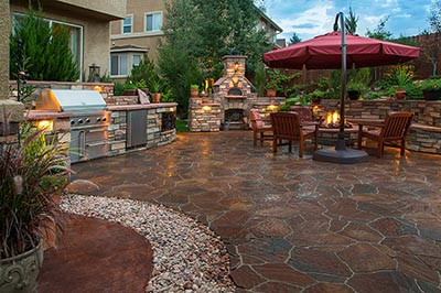 A patio with a barbecue, fire pit, and table with an umbrella