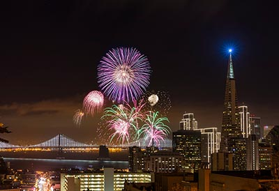 Fireworks at San Francisco downtown New Year. Bay bridge and downtown on the background.